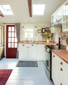 a simple (not too big) farmhouse kitchen. really well done home all together. exposed beams, butcher block counter tops, red door & painted floor