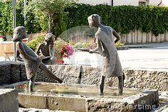 Photo made in the town of Fussen in Bavaria (Germany). In the image, made in one of the squares of the town, you see a nice fountain with statues of three girls, two who with his feet in the bath playing with water and the third one that, from the outside, is the observing.