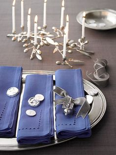 If your decorating style is contemporary, don't feel like your holiday table has to be fussy. To keep it simple, dress pewter or silver plates with blue napkins and sprinkle just a few embellishments at each place setting.