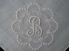 """A vintage white linen hankie with a """"B"""" monogram in a circle of tiny embroidered flowers – so very sweet and delicate. Measuring 12"""" square with a hand-rolled hem."""