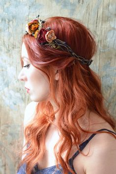 This rustic flower crown includes ranunculus in autumnal shades of burnt orange, dusty pink, and burgundy. Navy blue berry branches, tiny ferns,
