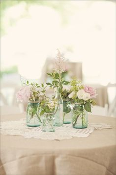 Reception tables - burlap table cloths, vintage lace doilies, and blue mason jars filled with peonies, astilbe, ranunculus, mint, ladies mantle, waxflower