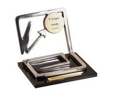 Peça: bidimensional, 11cm de altura. Materiais disponíveis: alumínio (prata) ou bronze (dourado ou patinado). Base: madeira natural ipê ou madeira revestida de fórmica preta, 14x17x1cm. Placa cortesia: aço inox (prata) ou latão (dourada), 9x1,5cm, placa superior 5,5 cm de diâmetro.