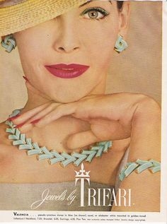 "1968 - TRIFARI - ADS - ""Valencia"" ... pseudo-precious stones in blue (as shown), coral, or alabaster white mooted in golden-tonrìed Trifanium! Necklace, 7,50; Bracelet, 5,00; Earrings, 4,00; Plus tax. Not authentic unless stamped Trifari. Jewelry design copyrighted."
