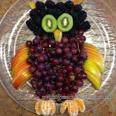 Owl Themed Birthday Party Fruit tray in the shape of an owl. Blackberries for the head, kiwi for eyes, halos for the beak and feet, apples for the wings and ears, and grapes for the body
