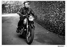 Such ease of style in this black & white photo of the man riding a motorcycle in Europe. Very vintage classic style & look, almost James Dean like.