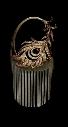 René Lalique | Horn comb with a gold shaft and jeweled phoenix feather. The decoration can be taken off the comb and worn as a brooch. The feather sports yellow sapphires, mandarin garnets, diamonds and receives pearl-shaped fire opal in the middle. The comb comes in its original box and is signed Lalique. c. 1902.