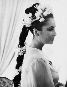 Elizabeth Taylor optait pour une tresse haute, piquée de jacinthes romaines et de muguet , pour son mariage avec Richard Burton en 1964. http://www.vogue.fr/mariage/beaute/diaporama/tresses-de-maries-coiffures-mariage/22472#elizabeth-taylor-optait-pour-une-tresse-haute-pique-de-jacinthes-romaines-et-de-muguet-pour-son-mariage-avec-richard-burton-en-1964