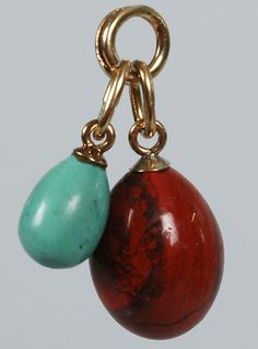 A pair of Faberge hardstone miniature pendant eggs, the red jasper egg pendant by Feodor Afanassiev, the marks on the turquoise egg illegible, both mounted in 56 standard gold, St Petersburg, circa 1900.