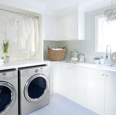 Laundry room with green glass subway tiles backsplash and white shaker cabinets. Silver front-load washer and dryer, laundry rod, glass canisters holding laundry detergent and West Elm Curved Basket. Crystal chandelier over laundry room sink. White Laundry Rooms, Laundry Room Sink, Laundry Room Storage, Laundry Room Design, Cabinet Storage, Laundry Area, Green Subway Tile, Glass Subway Tile, Subway Backsplash
