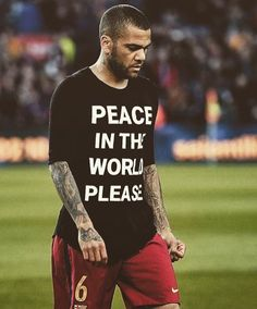 """Barcelona's Brazilian defender Dani Alves walks with a jersey that sporting the words, """"Peace in the world please"""" before the Spanish league """"Clasico"""" football match FC Barcelona vs Real Madrid CF at the Camp Nou stadium in Barcelona on April Barcelona Vs Real Madrid, Fc Barcelona, Football Match, Sport Football, Daniel Alves, Camp Nou, Professional Football, World Peace, Graphic Sweatshirt"""