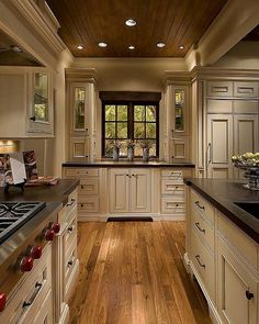 That is a large kitchen!! Cream cabinets Dark countertops Wood floor and ceiling. Like the style.