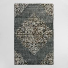 Handmade of 100% wool in a subtly distressed charcoal hue, our exclusive area rug features a tufted pile with a raised medallion design that adds a unique dimension and texture.