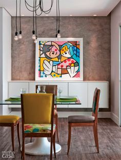 A parede da sala de jantar deste apartamento recebeu cimento queimado comum com uma demão de resina sintética. O ar rústico é quebrado pela tela colorida. O tampo de vidro incolor leva adesivo vinílico na face de baixo. Projeto de Cecília Guerra e Cristiane Tamburri.