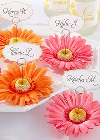 """Create a movable garden that brightens the day wherever it goes. Start with a color-rich array of gerbera daisy place card holders at your special occasion. Then watch your garden go and grow into photo holders in the homes of family, friends and neighbors!  Features and facts:  Gleaming metal place card holder with fabric gerbera daisy petals surrounding the daisy center  Coordinated place cards in included  Place card/photo holder is 4"""" h with card  Sold in sets of six"""
