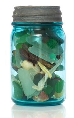 An antique canning Mason jar made of a beautiful shade of blue glass holds and displays a sea glass treasure.