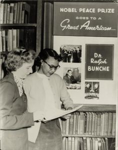 """Two women stand in a library in front of tribute to Dr. Ralph Bunche (1904-1971). In 1950 he became the first African American to be awarded the Nobel Peace Prize for his success in negotiating a truce to the Arab-Israeli conflict in 1949. by Charles """"Teenie"""" Harris"""