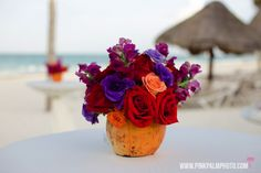 Coconut centerpiece filled with colorful florals for the cocktail hour. #mishkadesignsmexico #secretsmaroma