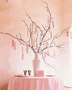 "guest book idea: Inspired by a Japanese custom, ask guests to tie their sentiments to tree branches with ribbons. Here, stems are adorned with crepe-paper buds and blossoms and placed in a porcelain vase. Expressions like ""Prosperity"" and ""Good Marriage"" are written in Korean and Japanese and hung ahead of time to decorate the branches."