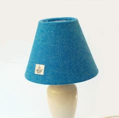 Here is a little lamp shade for a table lamp or wall light. It is a simple cone shape, inches) diameter at the top, inches) at the bottom, and inches) tall. The outside is a bright blue design of the world renowned Harris Twee. Table Lamp Shades, Harris Tweed, Wool Fabric, Blue Design, Lampshades, Christmas Fun, A Table, Wall Lights, September
