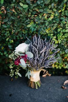 A unique bridal bouquet with a mix of dried lavender and fresh flowers in burgundy and Ivory, with silver dollar and seeded eucalyptus.