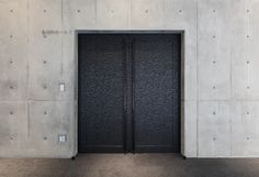 This handle's design helps highlight the profound impression created by the door and undressed concrete wall.