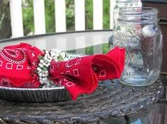 Table Setting Idea - Cutlery Roll Ups in Red Bandana Napkins using tin trays as plates and mason jars as glasses.