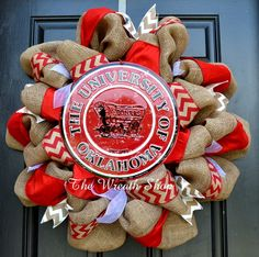 """With this University of Oklahoma Sooners Burlap Wreath, you can dress up your front door to cheer on your favorite alma mater this fall. This wreath is done on a high quality, natural jute burlap, and is accented with colored luxe ribbons and chevron ribbons.  It is finished off with a large, round, all-weather metal University of Oklahoma sign. These wreaths measure about 28"""" across and are made to order."""