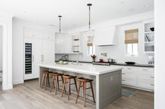 Glass and rope hand blown pendants illuminate a gray center island seating wood tractor stools at a white beveled countertop finished with a farmhouse sink with a polished nickel gooseneck faucet kit.