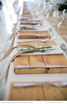 Rustic wood chargers, burlap ribbon and sprigs of rosemary.