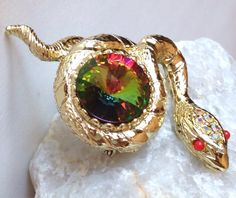 Gorgeous gold tone coiled snake brooch with a large watermelon rivoli center stone. Featured in Unsigned Beauties Of Costume Jewelry by Marcia