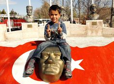 Passing through a small town in central Turkey, I was handing out finger puppets to some kids.  This boy casually walked over to a tribute to modern Turkey founder Ataturk, promptly sat on his head and played with the new toys.  ©Steve Gillick