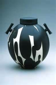 Sam Scott, American ceramic artist, is a functional potter who works predominantly in porcelain, although not from a traditional perspective.  His forms are defined by functional simplicity—the white surface of each piece is decorated with abstract designs in blues, browns, and grays. He is currently exploring the contrast of the white porcelain surface with a matte black glaze.