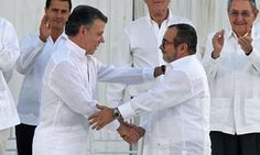 Colombian president Juan Manuel Santos, left, and Farc leader Timochenko shake hands during the signing of the historic peace agreement in Cartagena on Monday.
