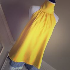 Eva Mendes Sunny Yellow Top Size M This is an Eva Mendes New York and Co top that is a beautiful bright sunny yellow. It ties in the back at the neck. It also is fully lined so you can't see through it (bonus :-)!!! It is a size small but I think it runs a little big so I would say more of a medium it would fit. Remember you can save $$$ by bundling on items and shipping!!! New York & Company Tops Blouses
