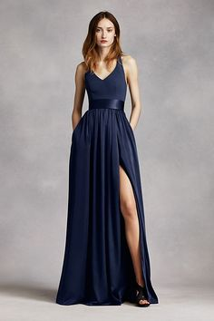 An exquisite gown that is perfect for a wedding party or any special event! V-neck halter gown with matte crepe bodice features bow detail at back. Long soft charmeuse skirt with middle slit an