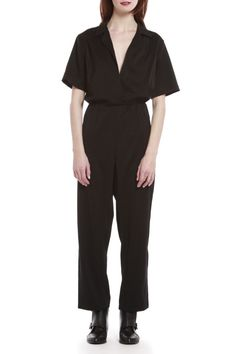 Black peg-legged jumpsuit, with a deep v-neck, wide-sleeves and a notched collar. Features an off-center snap closure overlap, and an elastic waistband.