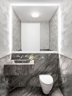 This powder room makes a dramatic statement with its dark-veined marble juxtaposed against a geometric light-gray wallcovering.