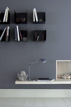salon avec mur peint en gris, étagères métalliques noires et cheminée blanche. Peinture de chez Little Greene