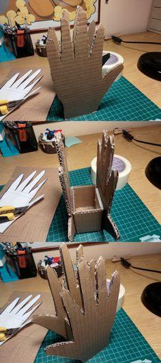 Un porta anells, fet reciclant cartró d'una capsa. Tres peces: les dues mans i la base.