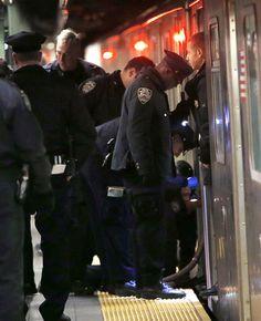22/Jan/2013 - Polícia de Nova York trabalha para retirar o corpo de uma pessoa não identificada debaixo de um trem do metrô em estação na Times Square.