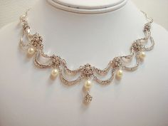 This beautiful necklace and earring set is created with rhinestone components paired with Swarovski ivory pearls. This is such a romantic design that sits high on your neck.