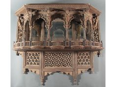 AN ANGLO-INDIAN SHELF BRACKET Punjab, Northern India, 19th century  carved wood, in the form of a pavilion, with lobed balustrade and mirrored back, the overhanging ceiling supported by caryatids and vyalas interspersed with cusped Mughal arches, geometric and vegetal fretwork panels on each side and below  55 x 65 x 25cm