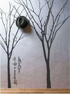 Wall painting trees behind coat rack - Woontrendz