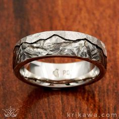 Choose your Mountain Range! At Krikawa, we hand-carve your favorite mountain range into your wedding band after you have selected your favorite metal. Pictured here in palladium with a textured sky. What mountain landscape has special meaning for you or a loved one?