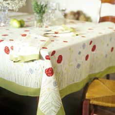 Bordered in light green, this easy-care cotton tablecloth brings multicolored garden blooms to your dining presentation. The cheery design sets a welcoming tone for spring and summer entertaining and everyday meals.