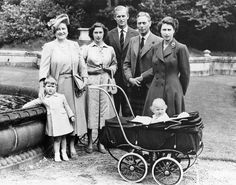 Princess Elizabeth, her husband Prince Phillip, and their children Prince Charles and Princess Anne, posing with her parents, the King and Queen of England.