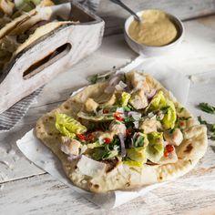 Lecker gebratenes Hähnchen, frischer Salat und pikantes Caesar-Dressing mit Anchovis und Knoblauch in einem lockeren Naan-Fladenbrot.