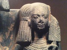 Khaemwaset, Ramesses II's son, with tightly twisted strands held together with a rosette decorated barrette, on an otherwise bald head. Maat's austrich feather added to a papyrus reed staff indicate that he held the title of Royal Scribe at Court. Schiste sculpture, Cairo Egyptian Museum.