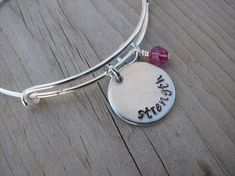 •A little inspiration and encouragement can go a long way. The bracelet is a lovely silver adjustable/expandable bangle bracelet. The 3/4 inch brushed silver pendant says, strength. 1 accent bead in your choice of colors, is included to add a little pop of color….choose a
